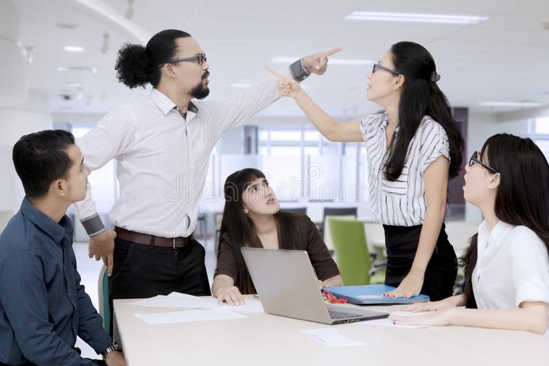 Business people pointing at each other having an argument in a group meeting stock photography