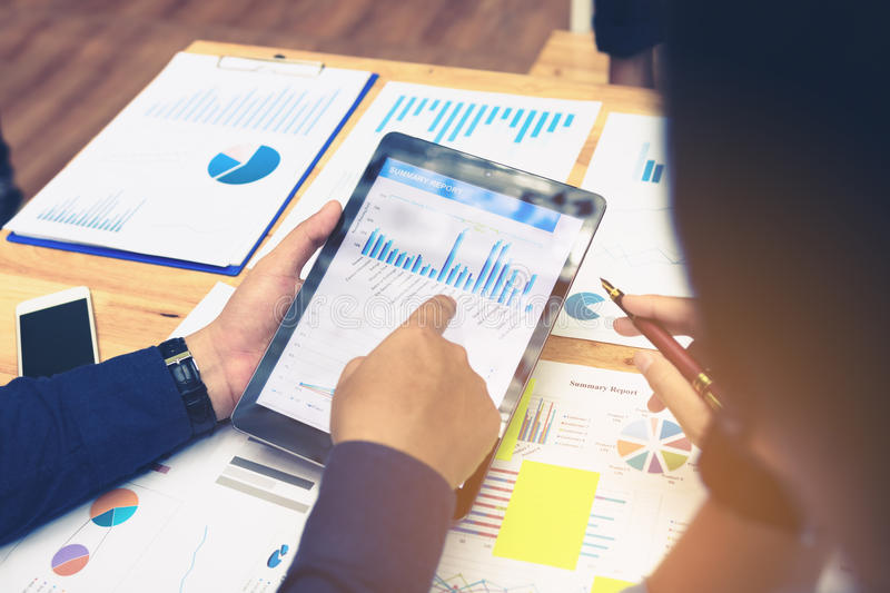 Business people pointing to tablet screen to looking graphs summary with earnings result data. royalty free stock images