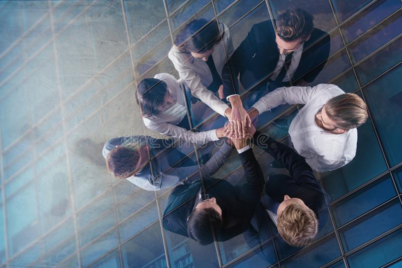 Business people putting their hands together. Concept of integration, teamwork and partnership. double exposure. Business people putting their hands together in royalty free stock image
