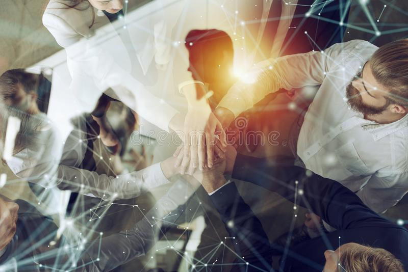 Business people putting their hands together. Concept of startup, integration, teamwork and partnership. Double exposure. Business people putting their hands stock images