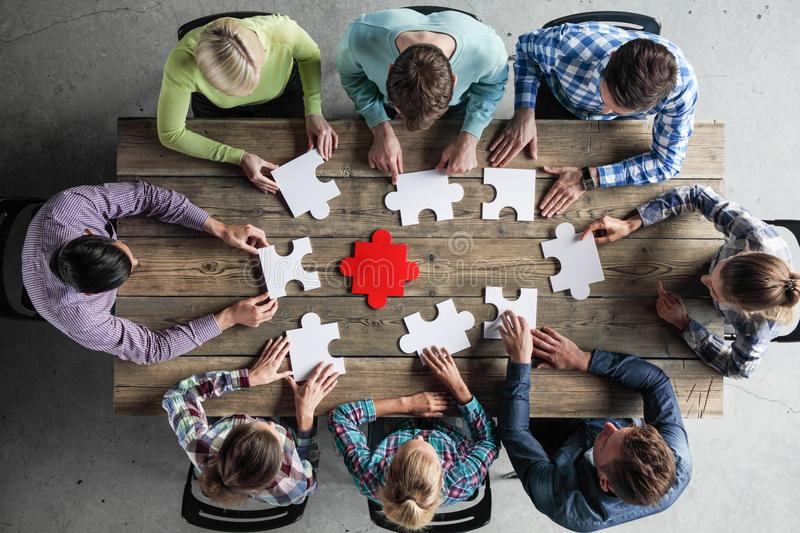 Business people and puzzle. On wooden table, teamwork concept stock photos