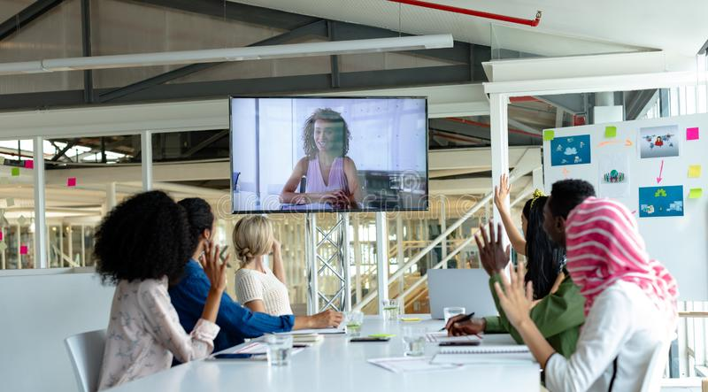 Business people raising hand during video conference at conference room in a modern office. Front view of diverse business people raising hand during video royalty free stock photos