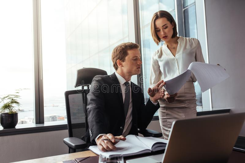 Business people reading documents in office stock image