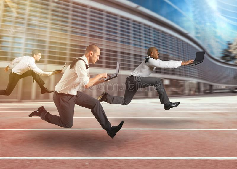 Business men working at full speed in a race track. Business people running with laptops on hands royalty free stock photos