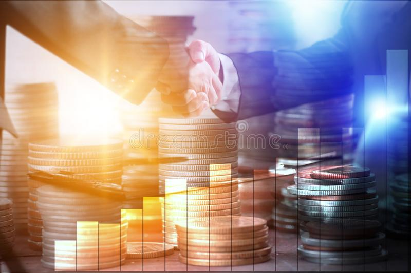 Business people shakes hand to invest with stacked money coins and finance graph, investment concept stock photography