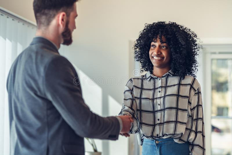 businesswoman making handshake with a businessman in office royalty free stock images