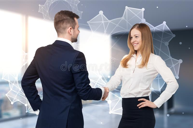 Business people shaking hands, cogwheels team. Businessman and businesswoman shaking hands in a modern office. Cogwheels and gears in the background. Teamwork stock photography