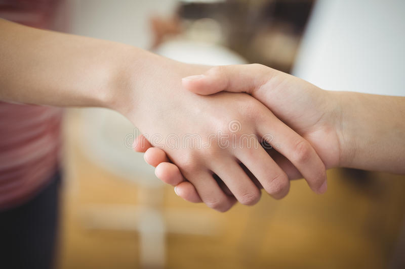 Business people shaking hands at creative office royalty free stock photos