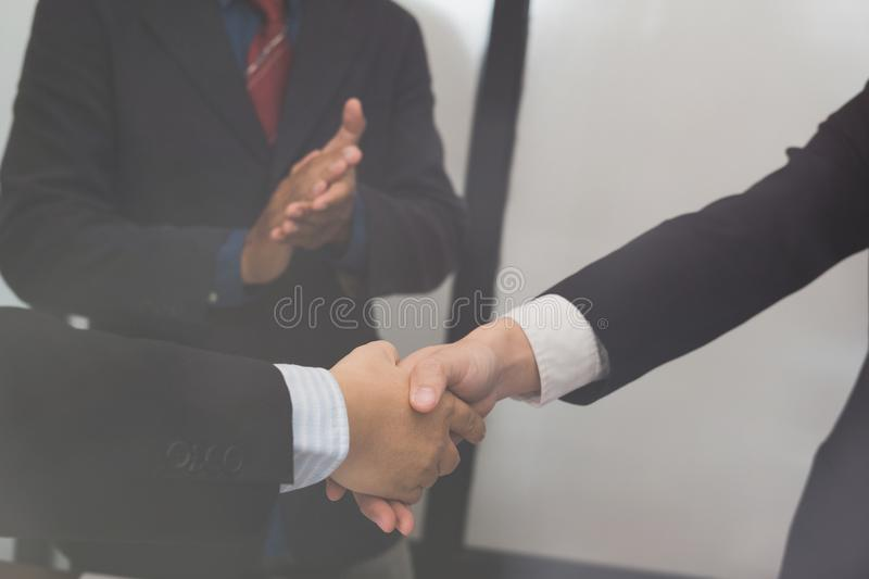 Business people shaking hands after finishing up meeting. co worker colleagues handshaking after conference. Greeting deal, teamwork, partnership royalty free stock photo