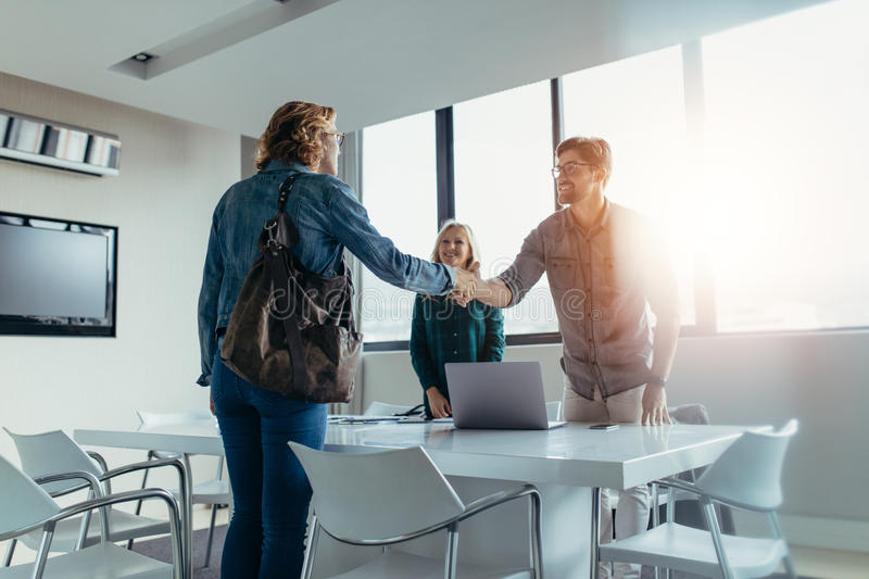 Business people shaking hands and finishing up meeting royalty free stock photo