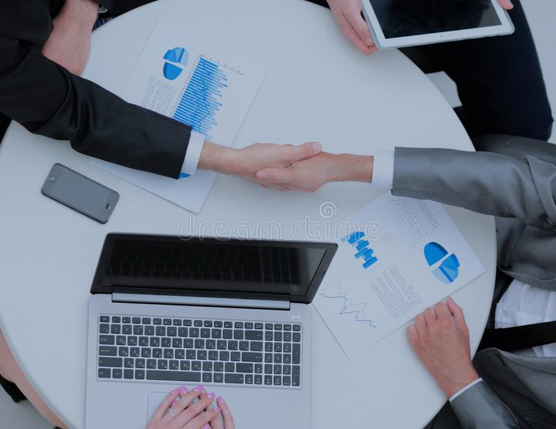 Successful businesspeople shaking hands in a modern office stock image