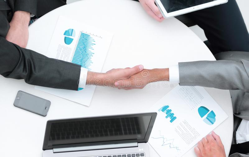 Successful businesspeople shaking hands in a modern office stock images