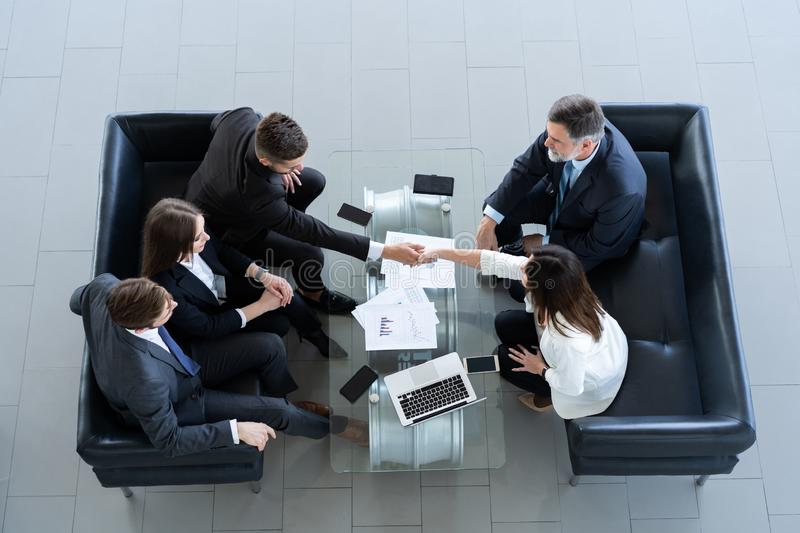 Business people shaking hands, finishing up a meeting, top view. stock photo