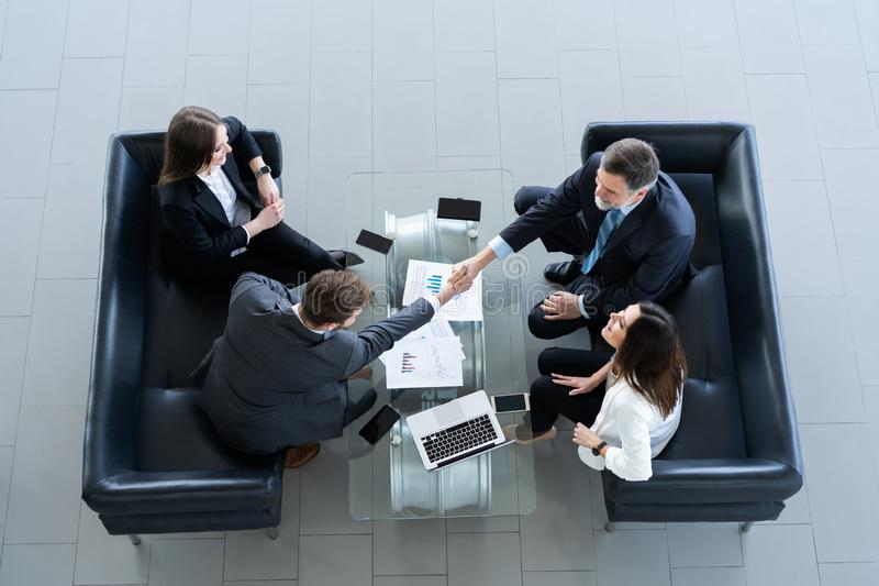 Business people shaking hands, finishing up a meeting, top view. royalty free stock image
