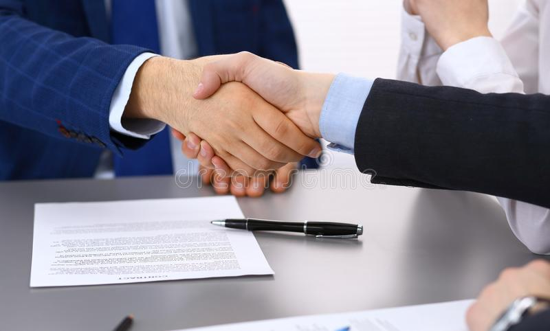 Business people shaking hands, finishing up a papers signing. Meeting, contract and lawyer consulting concept royalty free stock photo