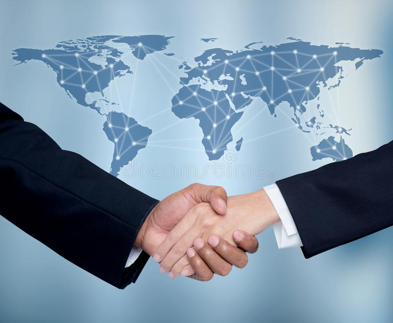 Business with people shaking hands with a global communication network stock photo
