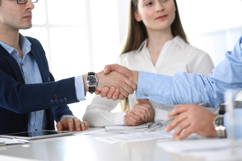Business people shaking hands at meeting or negotiation, close-up. Group of unknown businessmen and women in modern. Office. Teamwork, partnership and handshake royalty free stock images