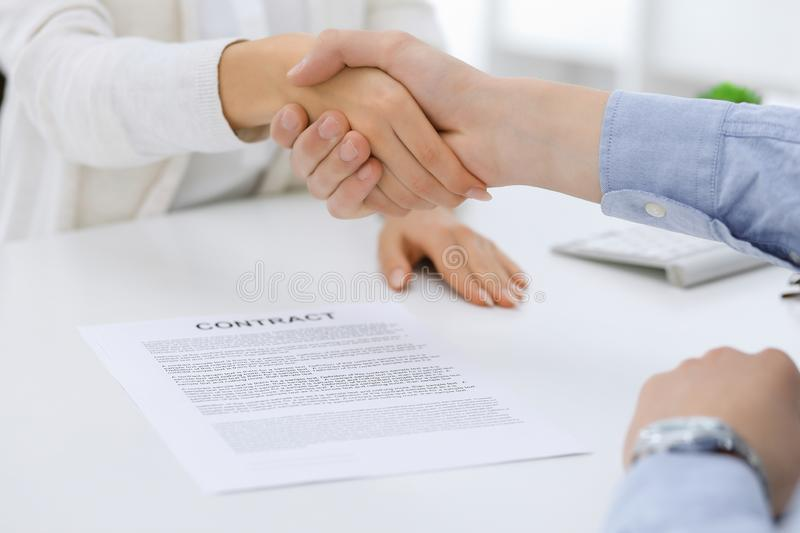Business people shaking hands at meeting or negotiation after contract discussing. Businessman and woman handshake at. Office while sitting at the desk. Success stock photo