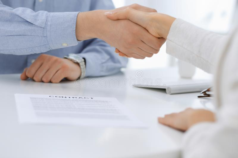 Business people shaking hands at meeting or negotiation after contract discussing. Businessman and woman handshake at. Office while sitting at the desk. Success stock photos