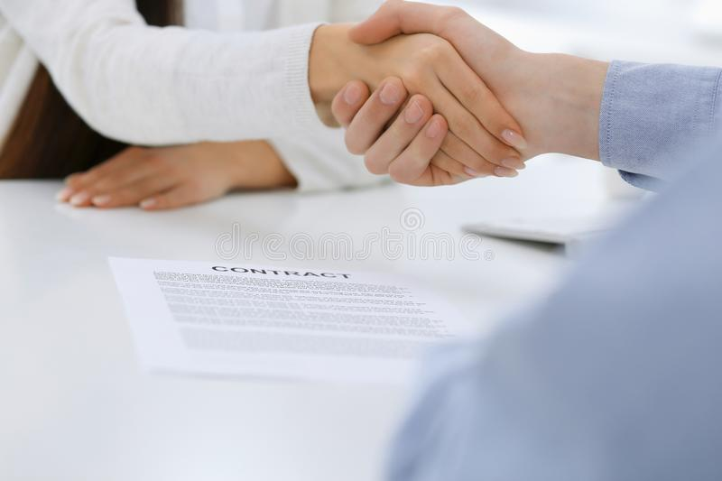 Business people shaking hands at meeting or negotiation after contract discussing. Businessman and woman handshake at. Office while sitting at the desk. Success royalty free stock photo