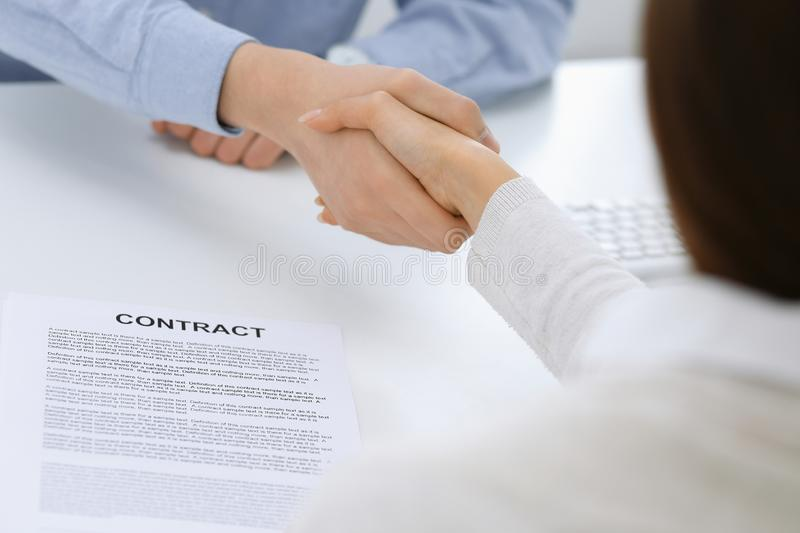 Business people shaking hands at meeting or negotiation after contract discussing. Businessman and woman handshake at. Office while sitting at the desk. Success stock photography