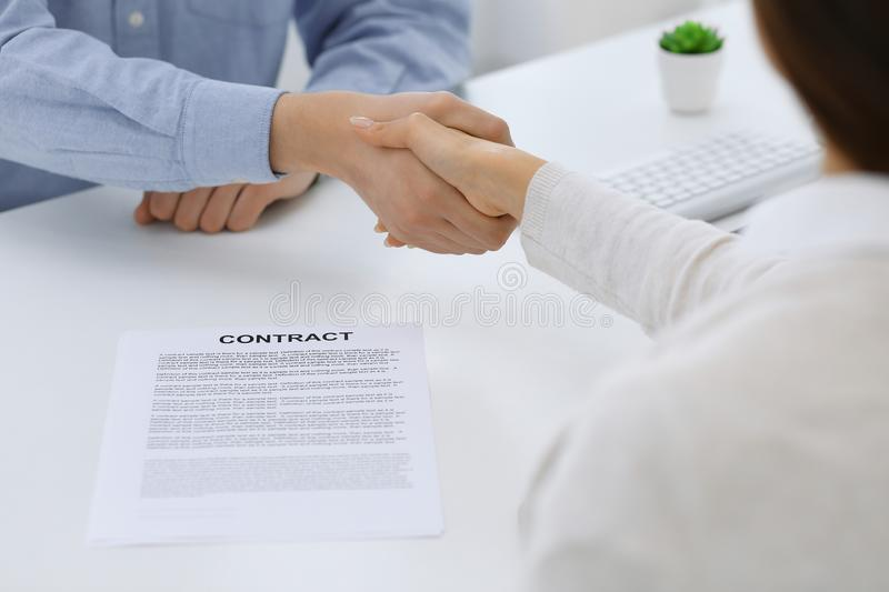 Business people shaking hands at meeting or negotiation after contract discussing. Businessman and woman handshake at. Office while sitting at the desk. Success stock image