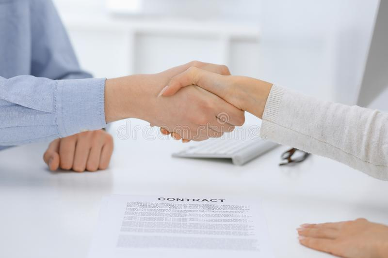 Business people shaking hands at meeting or negotiation after contract discussing. Businessman and woman handshake at office while stock images