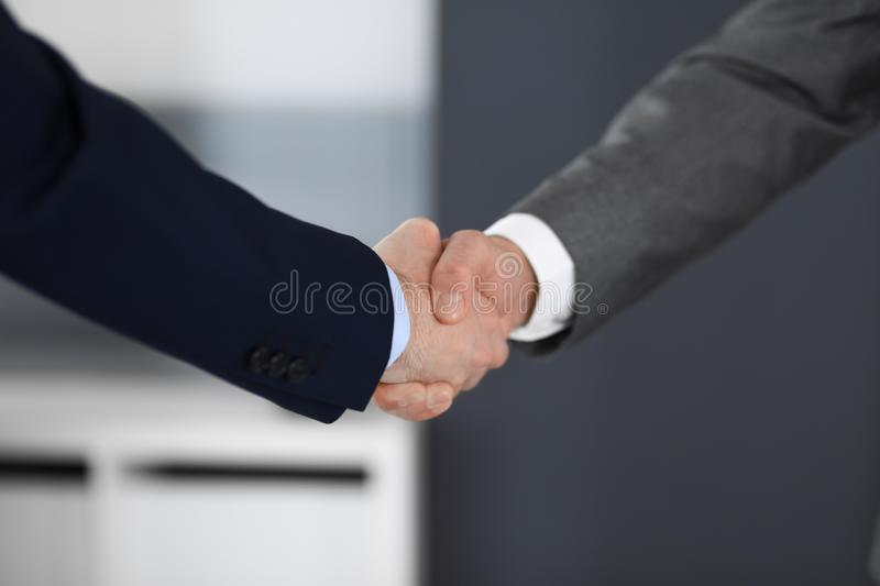 Business people shaking hands at meeting or negotiation in modern office, close-up. Teamwork, partnership and handshake stock images