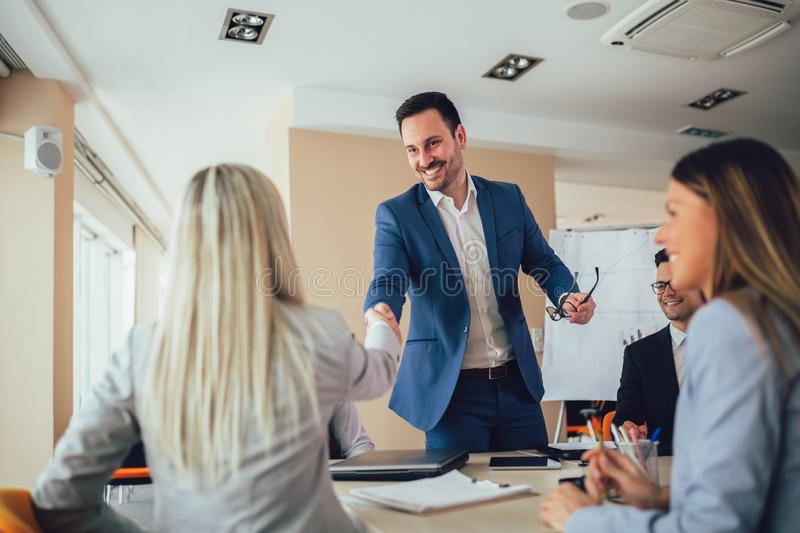 Business people shaking hands in meeting room. Selective focus royalty free stock image