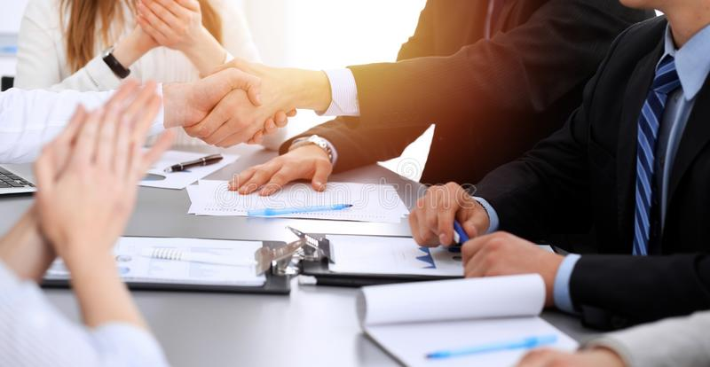 Business people shaking hands at meeting while theirs colleagues clapping and applauding. Group of unknown businessmen royalty free stock image