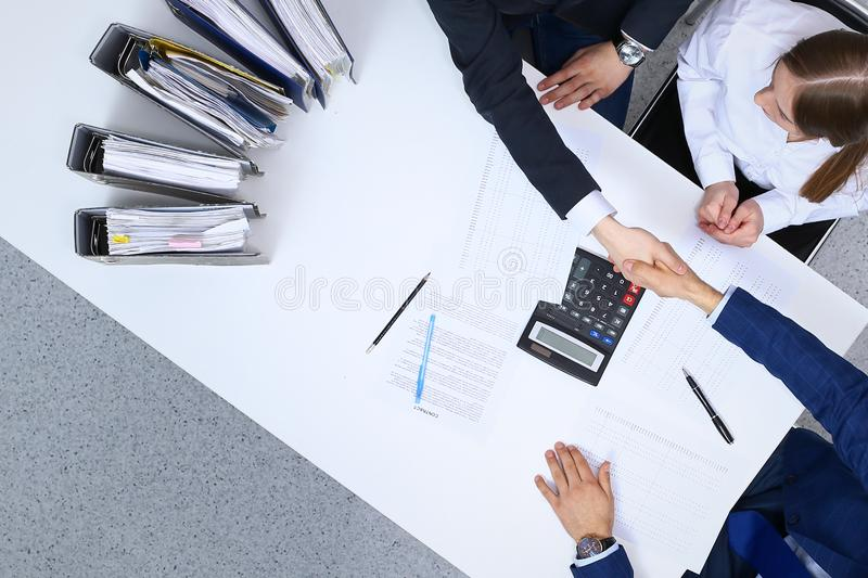Business people shaking hands at meeting, view from above. Bookkeeper or financial inspector making report, calculatin. G or checking balance. Internal Revenue royalty free stock image