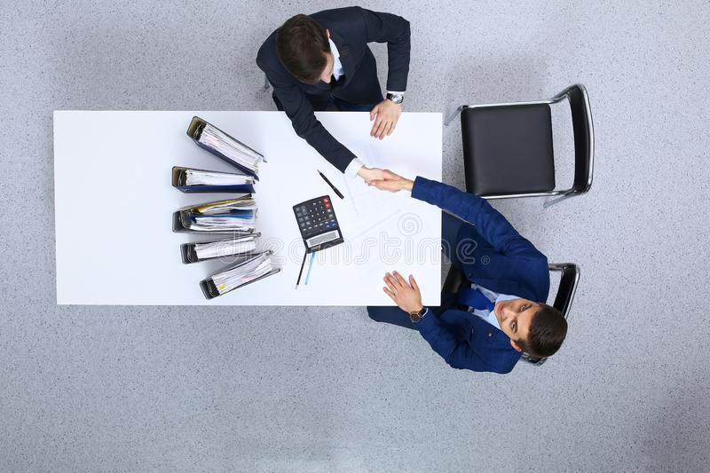 Business people shaking hands at meeting, view from above. Bookkeeper or financial inspector making report, calculatin. G or checking balance. Internal Revenue royalty free stock photo