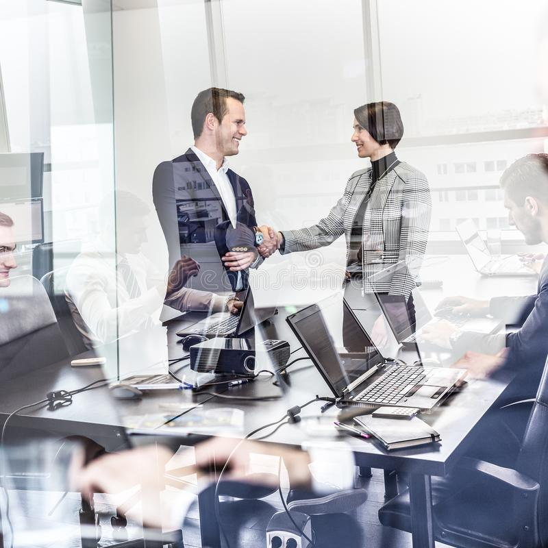 Business people shaking hands in moder corporate office. stock image