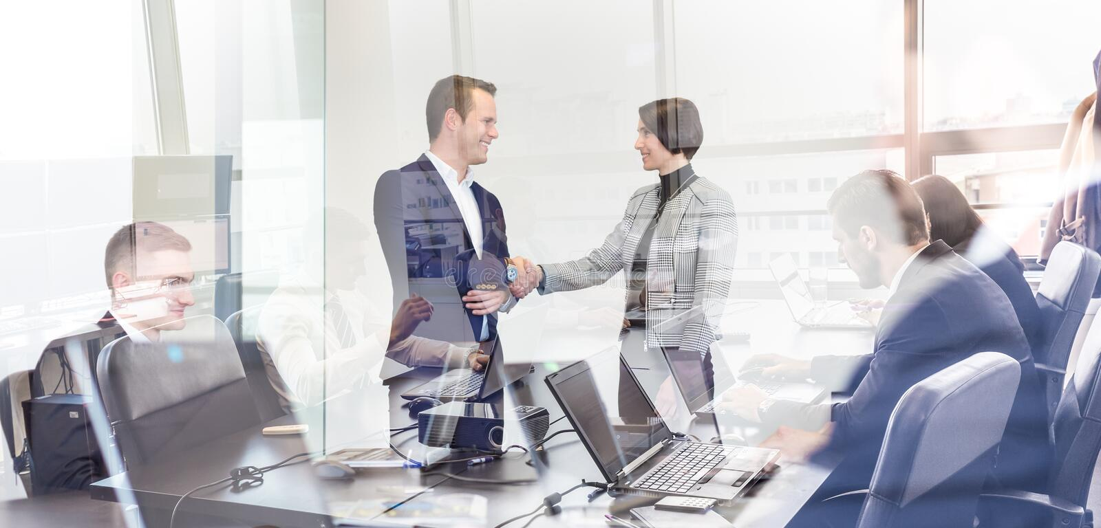 Business people shaking hands in moder corporate office. Sealing a deal. Business people shaking hands, finishing up meeting in corporate office. Businessmen stock photos