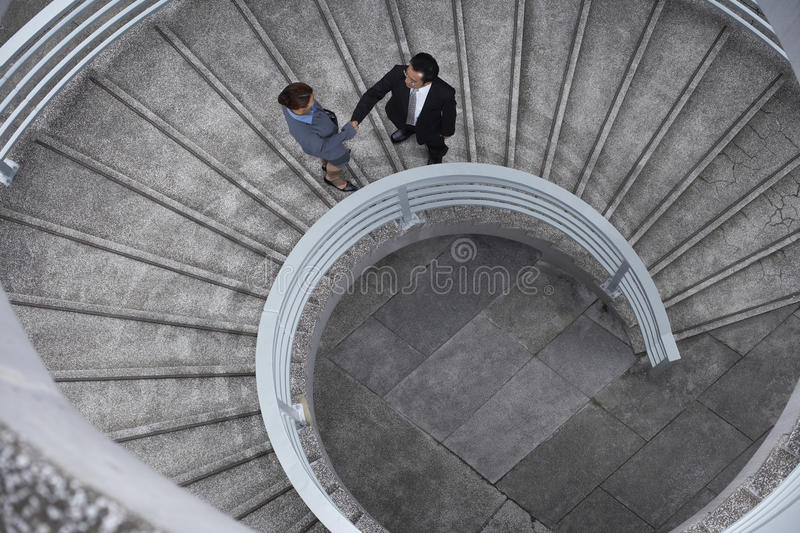 Business People Shaking Hands On Spiral Staircase. High angle view of businessman and businesswoman shaking hands on spiral staircase stock photo