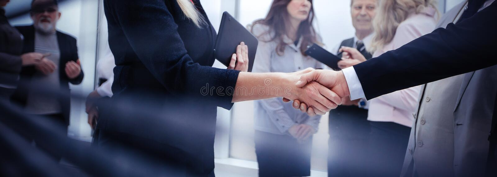 Business people shaking hands while standing near an office window royalty free stock photo