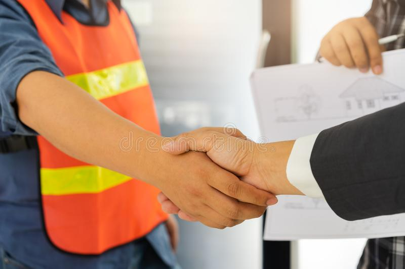Business people shaking hands after successful building construction planning project royalty free stock photo