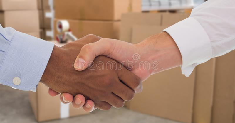Business people shaking hands in warehouse royalty free stock photography