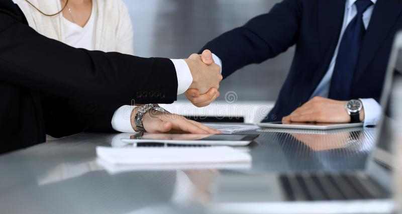 Business people shaking hands while working together at the glass desk in modern office. Unknown businessman, male entrepreneur wi stock image
