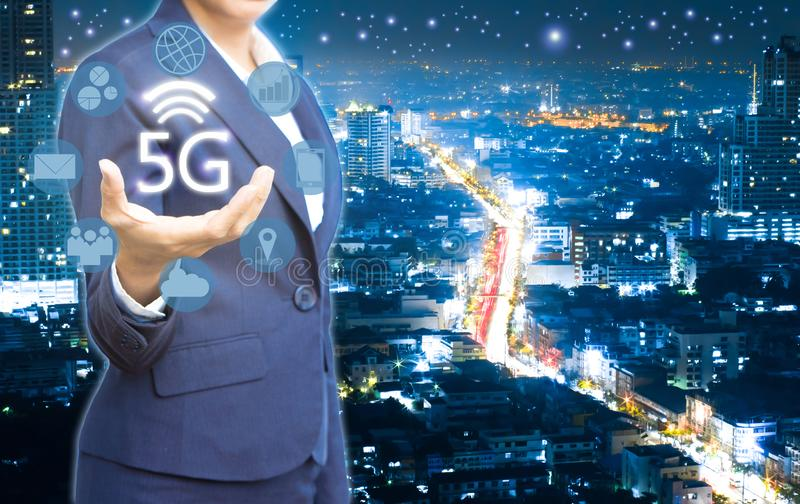 Business people showing 5g wireless and icon on city at the night time royalty free stock images
