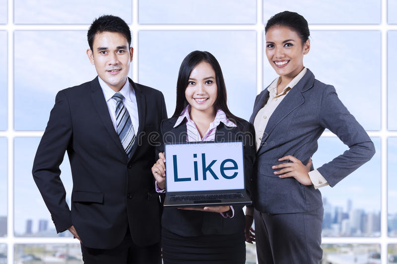 Business people showing like on laptop stock photography