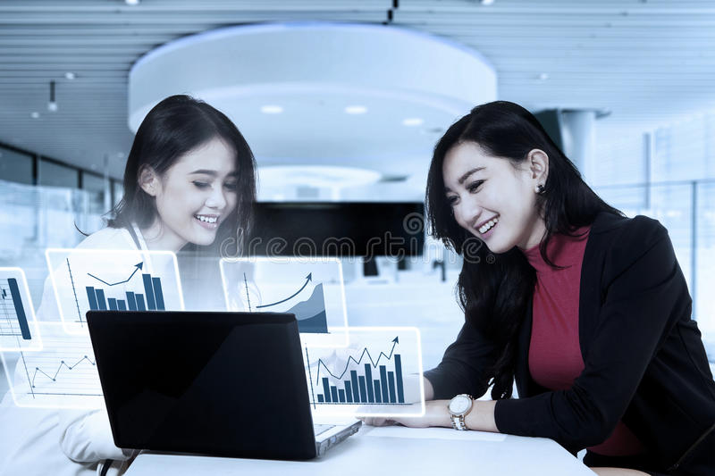 Business people showing report in the office. Image of business team showing report graphic of finance on the laptop while sitting and smiling in the office royalty free stock photography