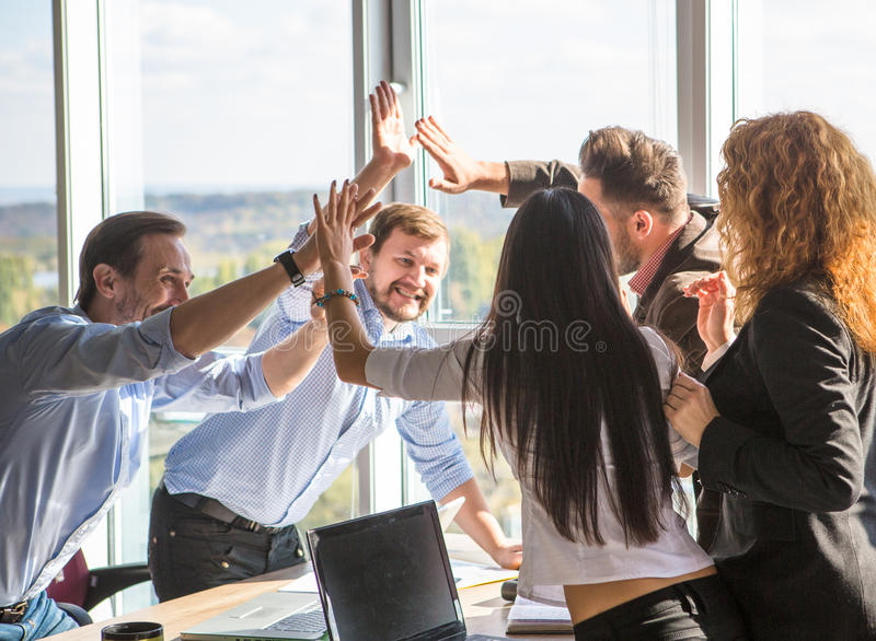 Business people showing team work in office. Business people showing team work and giving five after signing agreement or contract between companies, enterprises stock images