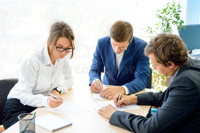 Business People Signing the Contract around the Table in Modern Office. Business Cooperation Concept. Business People Signing the Contract around the Table in royalty free stock image