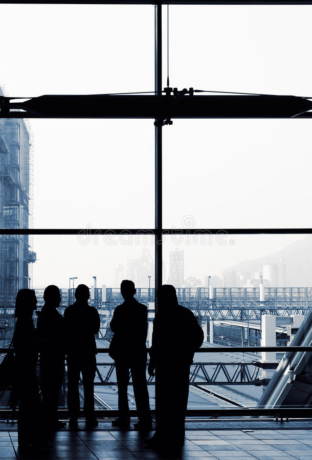 Business people silhouette. Standing front of windows in modern building stock photography