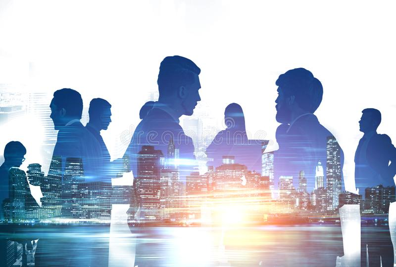 Business people silhouettes in night city. Silhouettes of diverse business people working together in night city. Concept of communication and teamwork. Toned stock photography