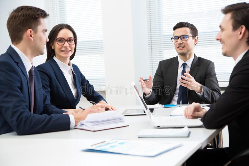 Business people are sitting around the table at a meeting in the office stock photography