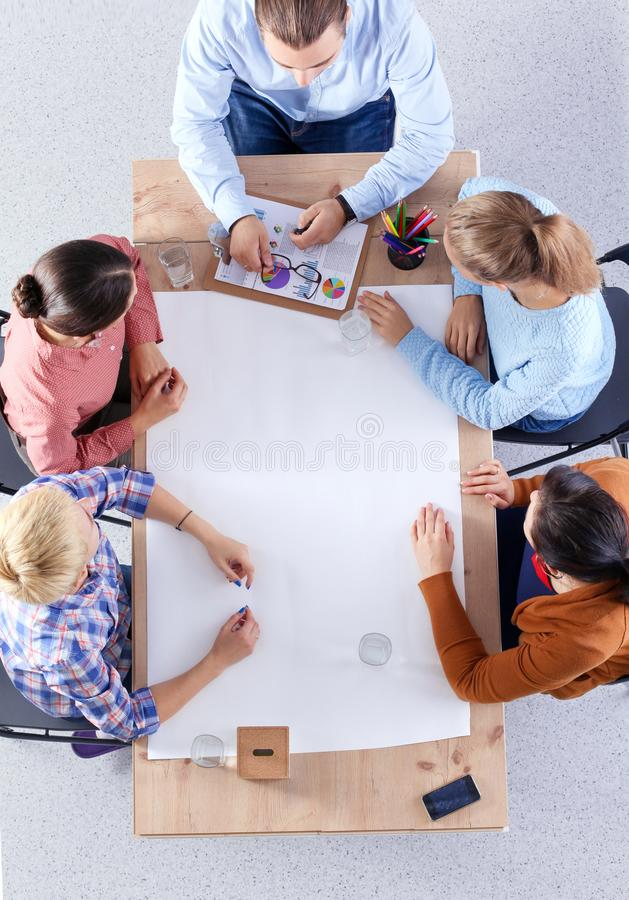 Business people sitting and discussing at meeting, in office stock images