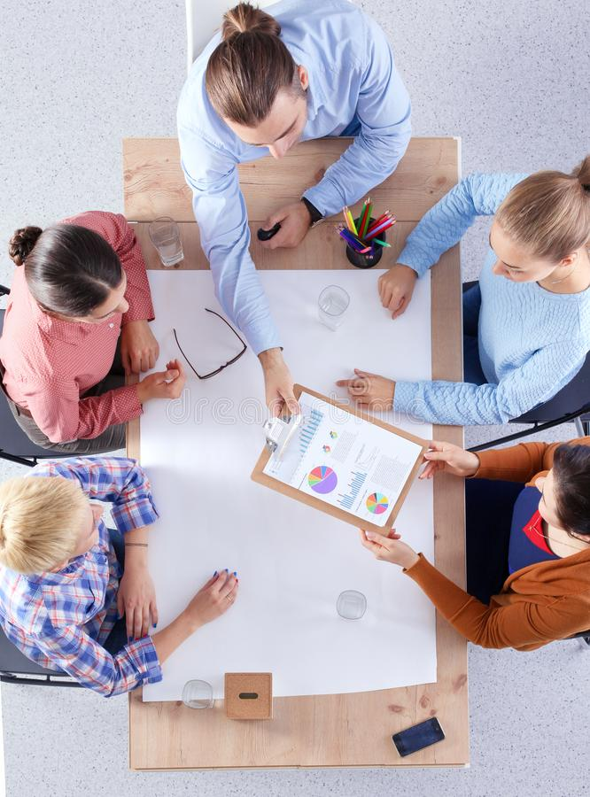 Business people sitting and discussing at meeting, in office stock photography