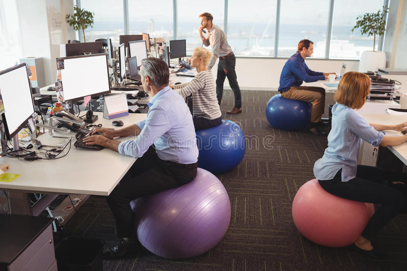 Business people sitting on exercise balls while working in office stock photo